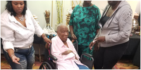 caregivers assisting a disabled old man