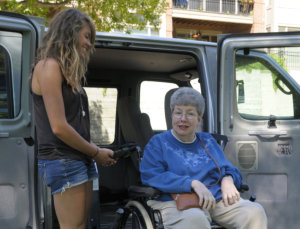 young woman assisting an old woman in a vehicle